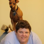 Miniature Pinscher standing on human.